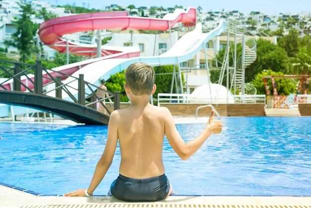 O menino está sentando-se na piscina lateral com água azul, férias de verão.