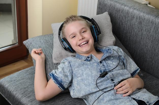O menino está sorrindo e ouve música no sofá em casa adolescente feliz e sorridente curtir música no sofá dentro de casa