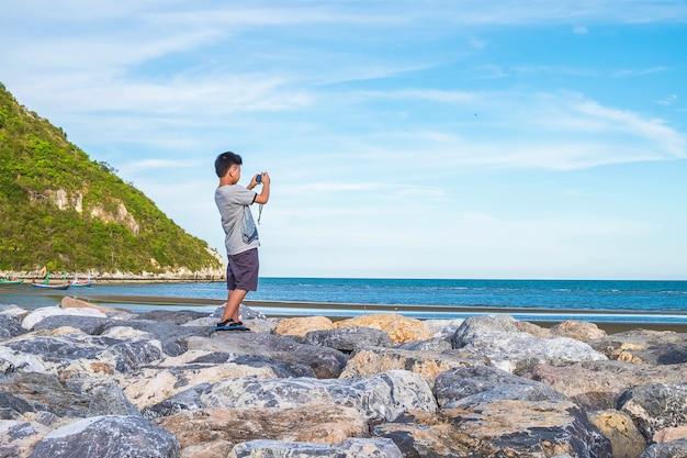 O menino está tirando fotos do mar no verão