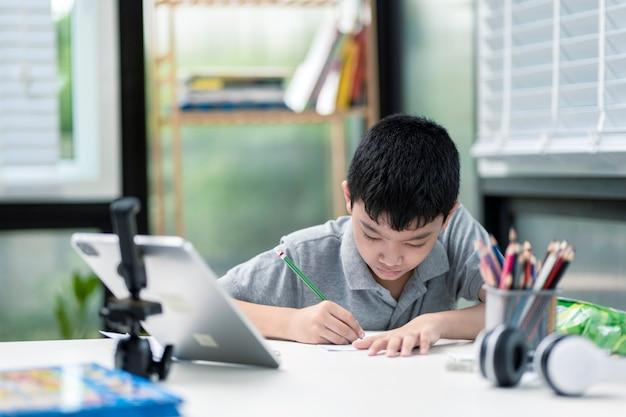O menino está usando a comunicação na internet em casa, ensinando em casa