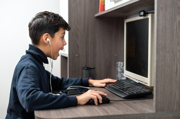 O menino está usando o pc com fones de ouvido. rosto feliz e animado