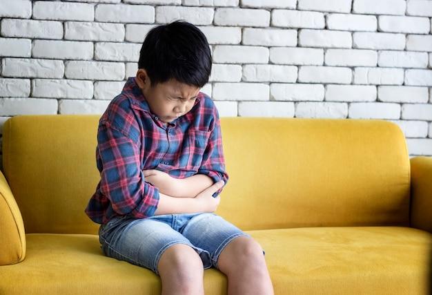 O menino estava sentado no sofá sentindo dor de estômago e estressado.