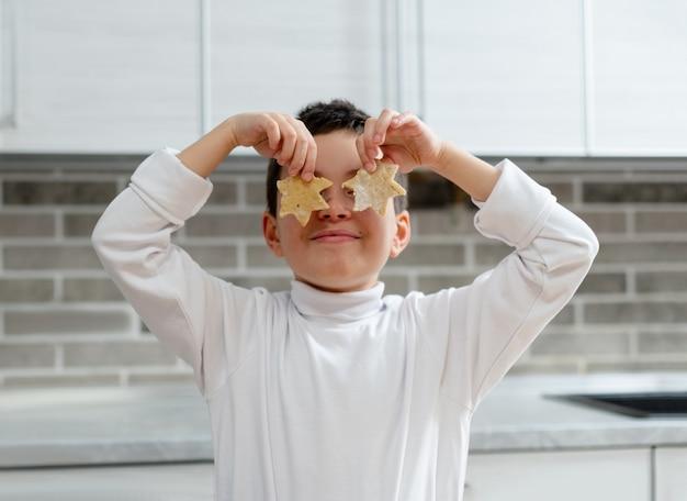 O menino estendeu duas estrelas da massa aos olhos imitando óculos