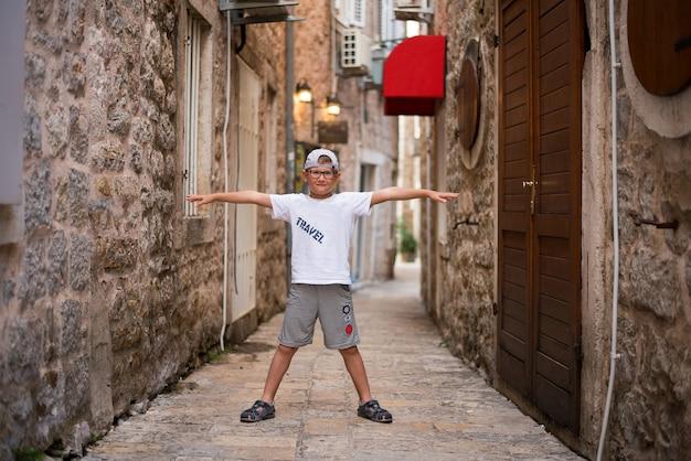 O menino esticou os braços pela rua estreita da cidade velha