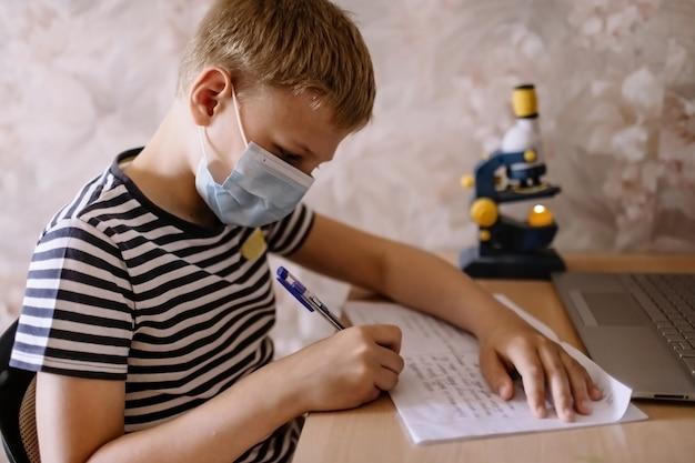 O menino estuda em casa, usa máscara protetora e faz a lição de casa. educação online de ensino à distância.