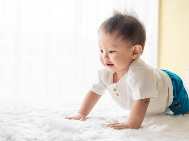 O menino feliz do retrato está rastejando no tapete branco na sala.