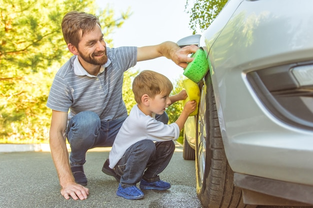 O menino feliz e um pai limpam a roda de um carro