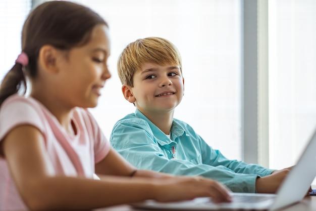 O menino feliz e uma menina sentados à mesa