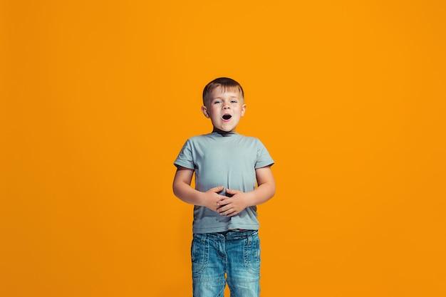 O menino feliz em pé e sorrindo contra a parede laranja