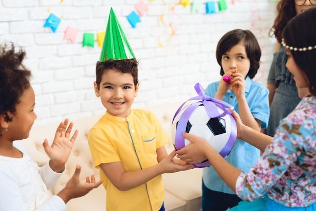 O menino feliz recebe a bola do futebol como o presente de aniversário.