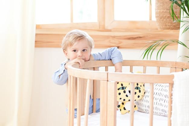 O menino fica ao lado da cama no berçário e tem um brinquedo nas mãos. o garoto está no jardim de infância e brinca. decoração de quarto infantil ecológico em estilo escandinavo. o garoto está em casa.