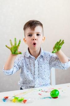O menino fica surpreso ao mostrar as mãos manchadas e manchadas de verde e, em cima da mesa, há um ovo de páscoa e tintas.
