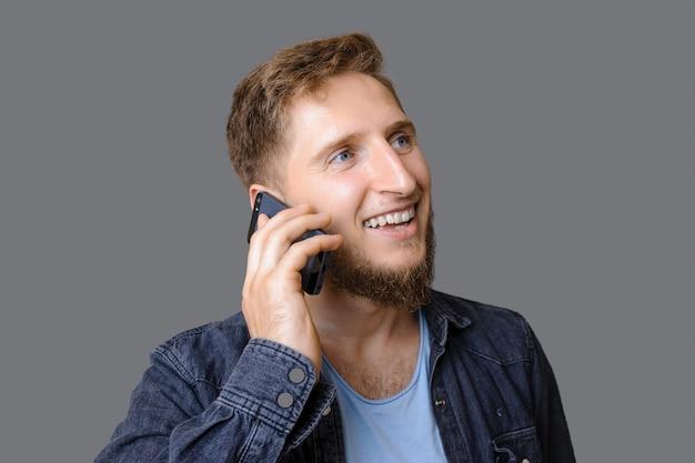 O menino ginger está falando ao telefone e sorrindo perto do espaço livre do estúdio cinza