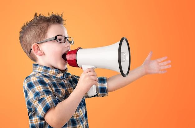 O menino grita em um megafone em um fundo sólido