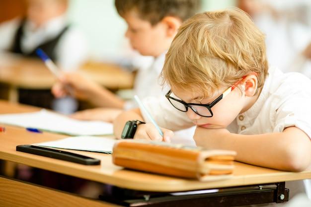 O menino inteligente bonito feliz está sentando-se em uma mesa em uns vidros com levantamento da mão. de volta à escola