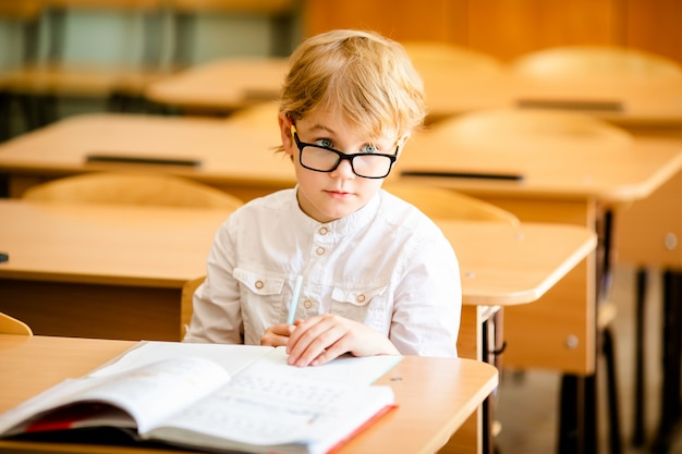O menino inteligente bonito feliz está sentando-se em uma mesa em uns vidros com levantamento da mão.