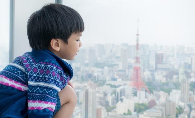 O menino japonês está olhando para tóquio para o futuro