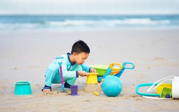 O menino joga a pá e os brinquedos na areia da praia apenas com o feliz no conceito das férias de verão com espaço da cópia
