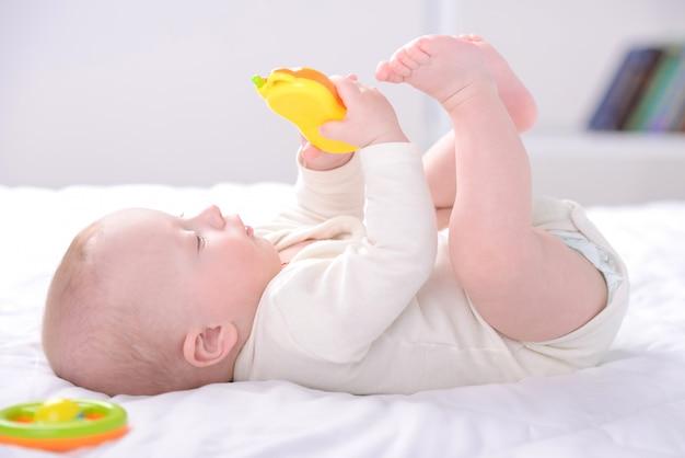 O menino joga brinquedos no berço.