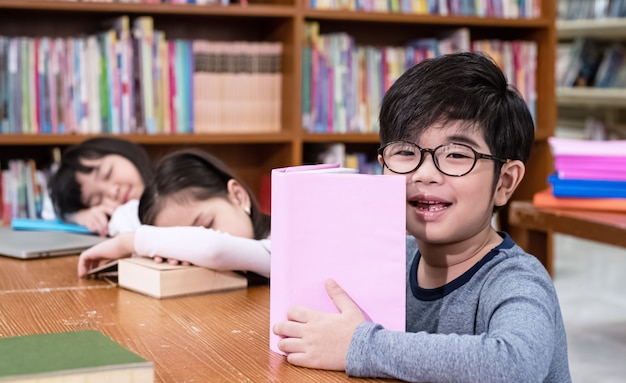 O menino lendo livro com sentimento feliz, na frente de meninas dormindo turva, na biblioteca, luz embaçada ao redor