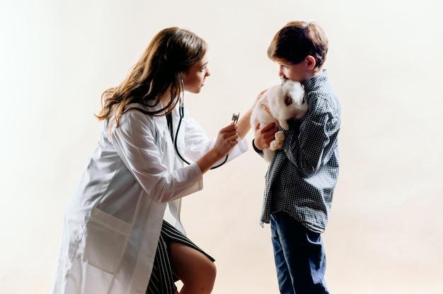 O menino levou seu coelho ao veterinário para exame, o veterinário faz um exame
