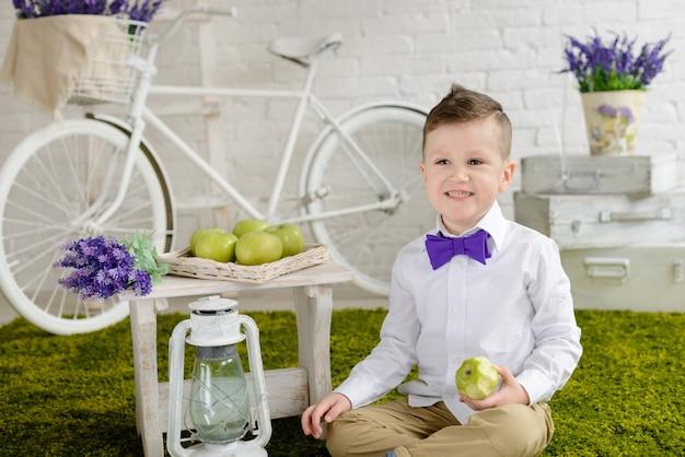 O menino lindo com um penteado e um buquê azul de flores