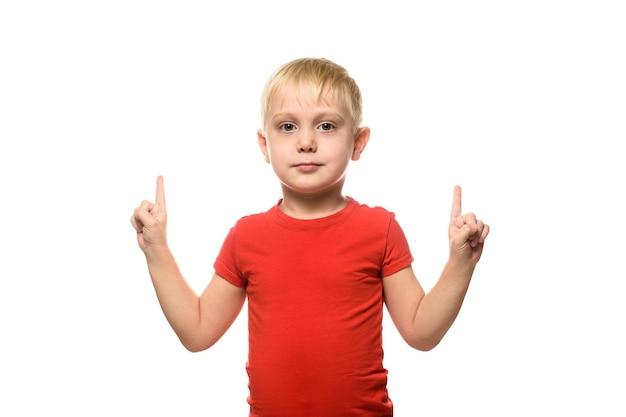 O menino loiro com uma camiseta vermelha está de pé e apontando para cima com os dedos indicadores