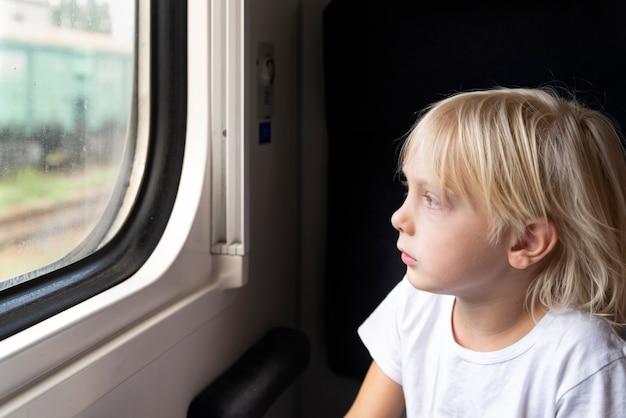 O menino loiro olha pensativo pela janela do trem. viagem de trem.