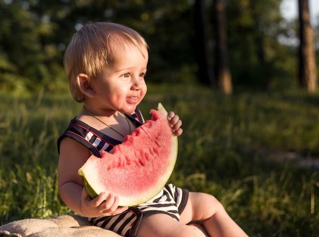 O menino louro do bebê come a melancia e sorri.