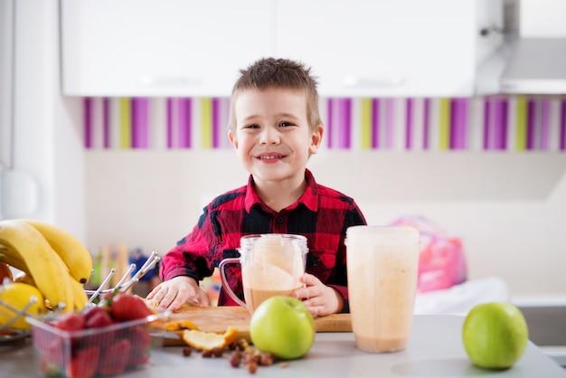 O menino masculino feliz novo em uma camisa vermelha está bebendo o batido de fruta ao sentar-se no balcão perto da janela em uma cozinha muito brilhante.
