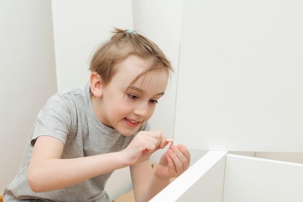 O menino monta uma estante sozinho. filho ajudando o pai a montar móveis novos em casa. montagem de móveis por conta própria.