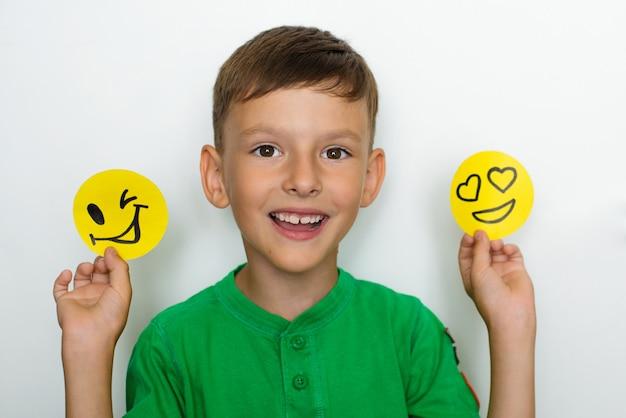 O menino mostra emoções e segura sorrisos engraçados feitos de papel