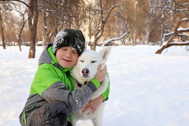 O menino mostra ternura ao seu amado cachorro no inverno na natureza.
