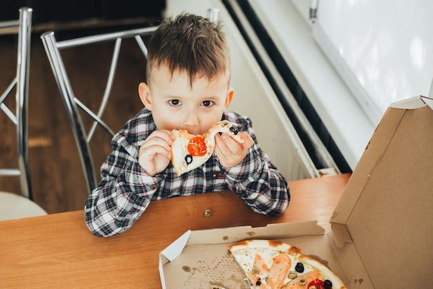 O menino na cozinha em casa comendo pizza com salmão