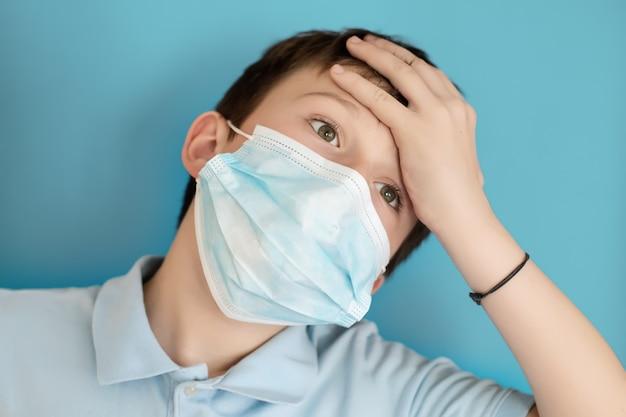O menino na máscara protetora médica agarrou a cabeça. criança tem dor de cabeça. sintoma de coronavírus.