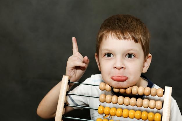 O menino na surpresa espalhou seus braços perto do ábaco de madeira.
