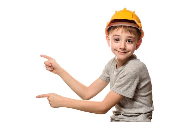 O menino no capacete alaranjado da construção mostra os dedos indicadores de lado. retrato. isolar na parede branca.