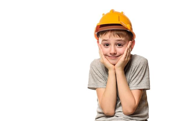 O menino no capacete alaranjado da construção pôs as mãos na bochecha. retrato. isolar na parede branca.