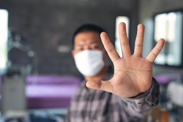O menino novo está waring a máscara e está fazendo o sinal da mão da parada isolado no hospital.