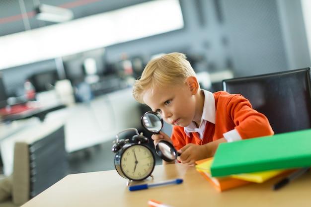 O menino novo senta-se na mesa no escritório