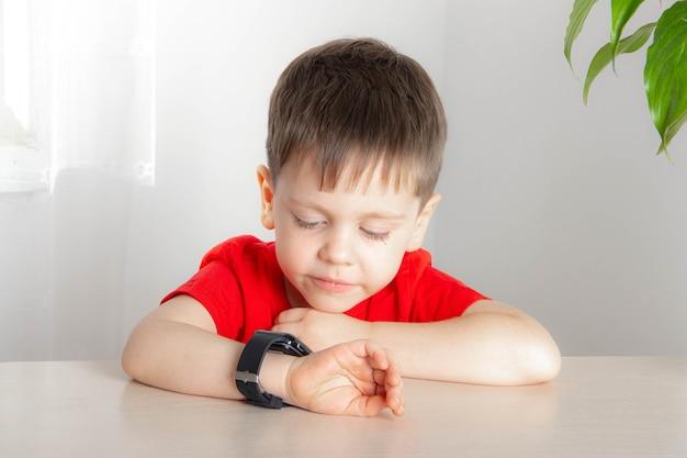 O menino olha a hora no relógio
