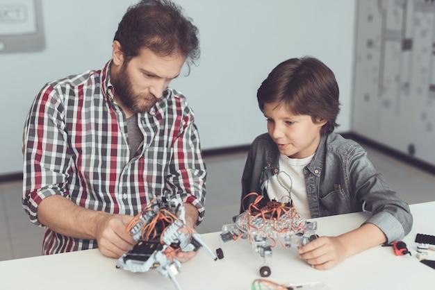 O menino olha com cuidado enquanto um homem recolhe um robô