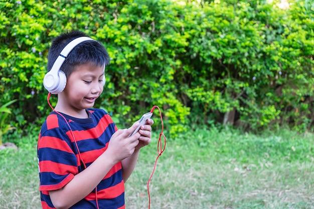 O menino ouvindo música com fones de ouvido e telefone inteligente mão segure