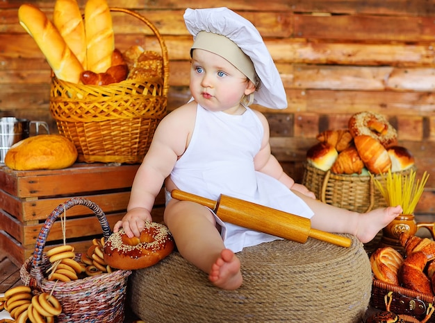 O menino padeiro com um chapéu e avental de chef com um grande bagel nas mãos sorri no contexto de produtos de panificação
