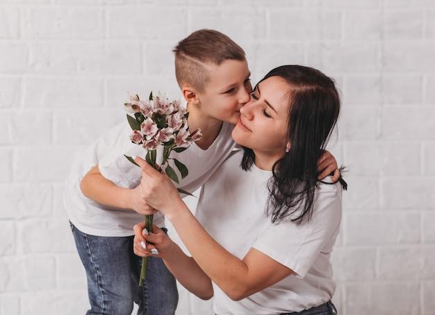 O menino parabeniza a mãe e dá flores para ela