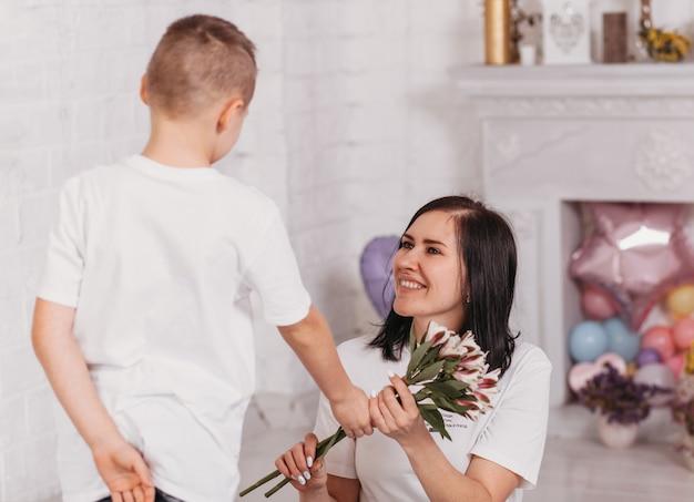 O menino parabeniza sua mãe e lhe dá flores. aniversário, dia das mães
