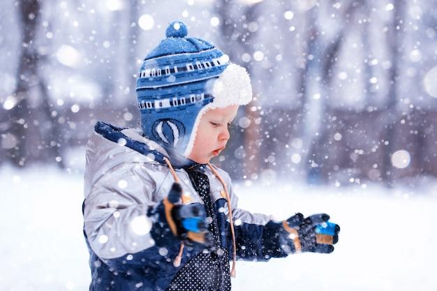 O menino pega flocos de neve na tarde gelada de inverno, imagem enfraquecida