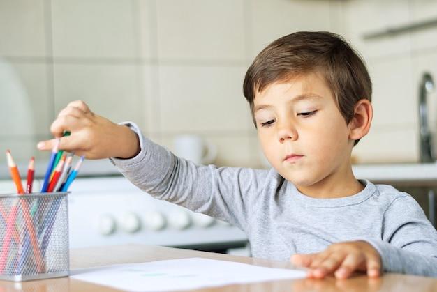 O menino pega um lápis na mão para fazer desenhos infantis no papel.