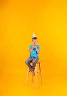 O menino pequeno está sentado em uma cadeira alta com um boné de férias de papel e um apito sobre um fundo amarelo