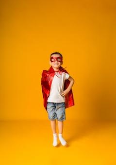 O menino pequeno fantasiado de herói, com uma máscara vermelha e uma capa, salta sobre uma superfície amarela com espaço para texto